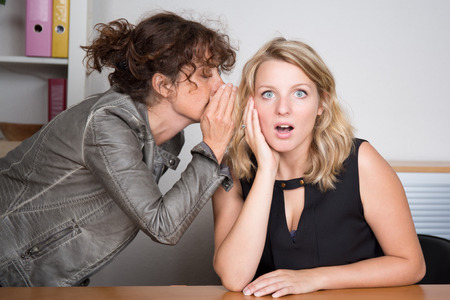 stupor: one girl whispers bad news to another girl - Shocking Secrets Stock Photo