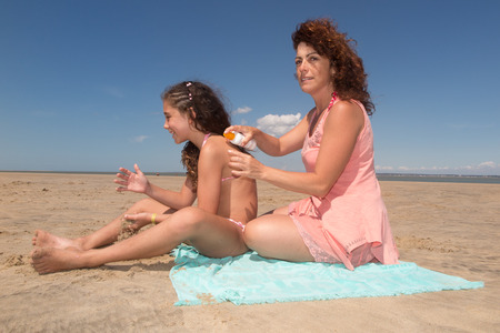 putting: Mother And Daughter Putting On Sun Cream