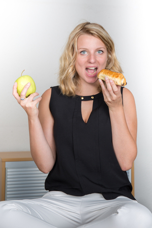 hesitating: Thoughtful young blonde woman hesitating between a fruit and chocolate