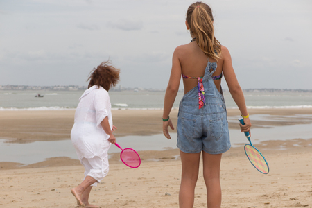 grand kid: Kid and grand mother playing on the beach