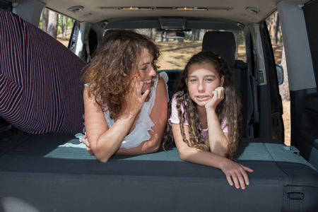 to depart: mother and daughter in  trunk of car ready to depart for holidays