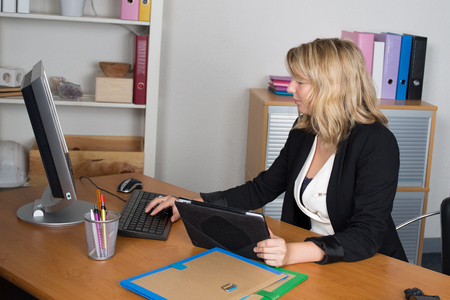 phoning: Young businesswoman, phoning at the office, with a worried expression on her face. Stock Photo
