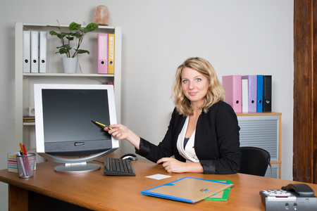 Happy business woman showing computer blank screen Stock Photo
