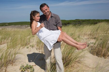 Father having fun with a young girl at summer