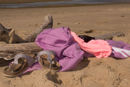 flip flops: Rolled up beach towels and sandals or flip flops on a beach.