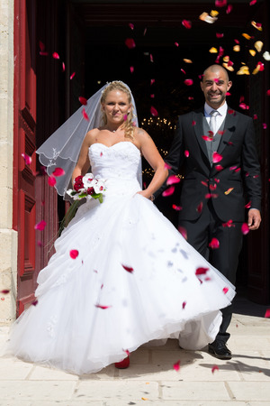 walking in the rain: Just married couple under a rain of rose petals
