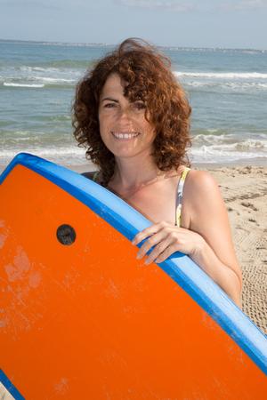 bodyboard: Woman  having fun bodyboarding under sun and blue sky