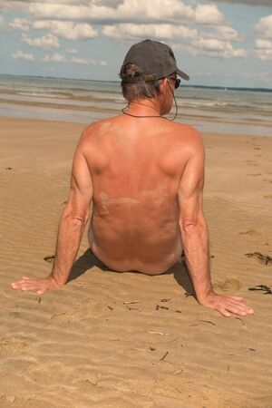 naturist: Man with  sits on the coast and looks at the sea. naturist