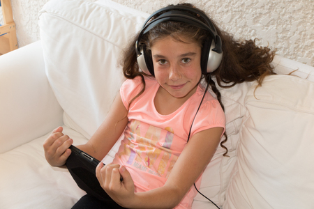 youthfulness: Girl inside with a tablet and listen to music on headphones