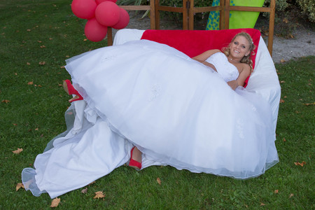 red sofa: Crazy blond bride on the red sofa happy Stock Photo