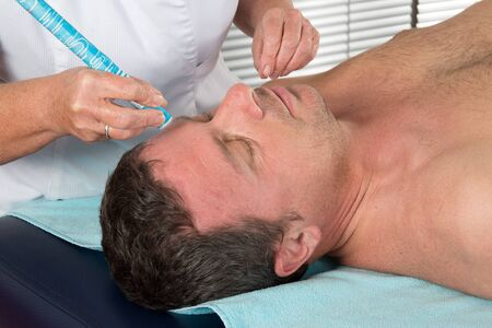 Alternative medicine therapist doing moxa treatment on her client Stock Photo