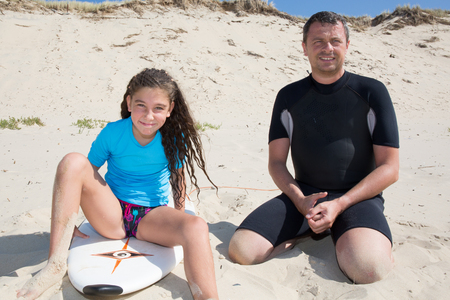 teaching adult: Cheerful father and daughter surfing in the ocean