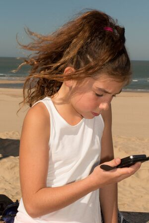 modern generation: Portrait of a cute young girl playing with smart phone on the beach. Modern lifestyle, modern generation concept.
