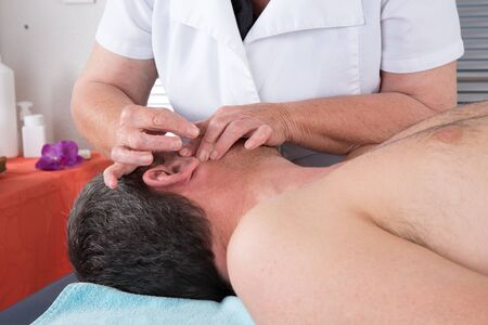 ear acupuncture: Man in an acupuncture therapy at the health spa