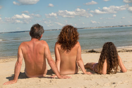 Lovely naturist family, parents and daughter have fun on holidays Stock Photo