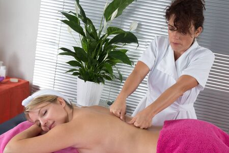 female therapist: Blond young girl having a massage by a female therapist Stock Photo