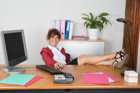 at her desk: Woman relaxing at her desk at office Stock Photo