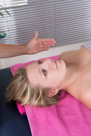 reiki: The hand of therapist healing a blond young woman -reiki therapy