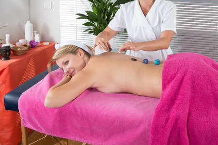 crystal therapy: Young blond woman at crystal healing session in therapy room Stock Photo