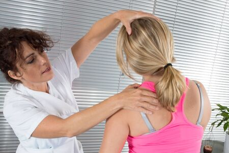 backpain: Professional female physiotherapist giving shoulder massage to woman in hospital