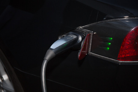 Black electric car charging: Close-up of indistinguishable electric car 'fueling', i.e. plugged to the electricity hose, charging battery. Stock Photo