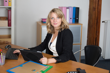 office women: Young blond and pretty girl working on tablet at work