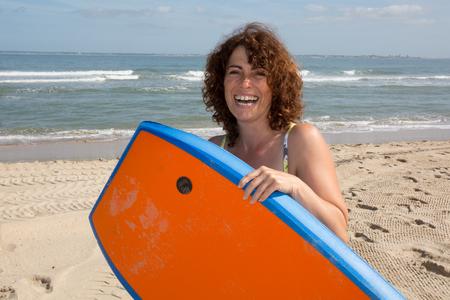 bodyboarding: Woman  having fun bodyboarding under sun and blue sky