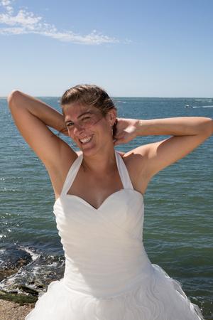 femme mari�e: A married woman bride in her wedding dress in sunshine on a beautiful tropical beach