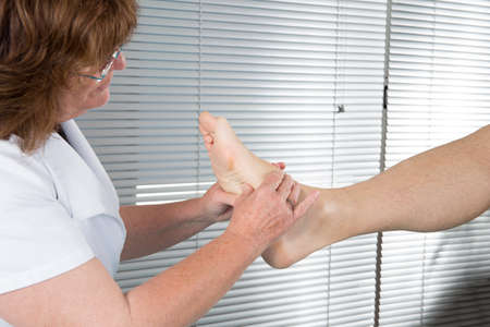 podiatry: Close up of physiotherapist massaging female foot