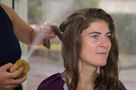 pinning: Stylist pinning up a womans hairstyle at a beauty saloon