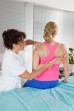 giving back: physiotherapist giving back massage to woman in hospital Stock Photo