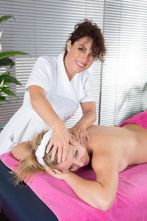 dowsing: Alternative medicine therapist using crystal to make a massage Stock Photo
