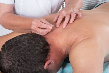 massage therapy: Man in an acupuncture therapy in a Spa center