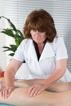 leg calf injury: Physiotherapist doing calf massage to her patient in medical office