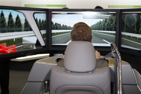 Man in a car simulator in a congress for safety