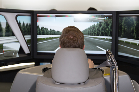 simulator: Male is trying a car simulator in a congress