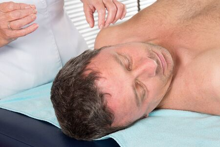 acupuncture: Adult physiotherapist is doing acupuncture on the back of a male patient.