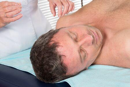 acupuntura china: Fisioterapeuta adulto est� haciendo la acupuntura en la parte posterior de un paciente de sexo masculino. Foto de archivo