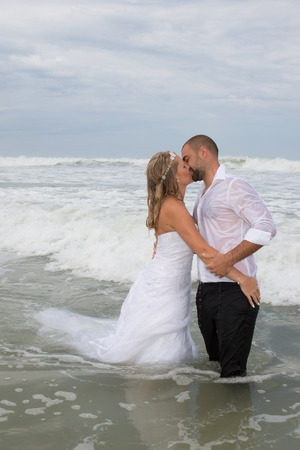 ocean and sea: An attractive bride and groom getting married by the beach