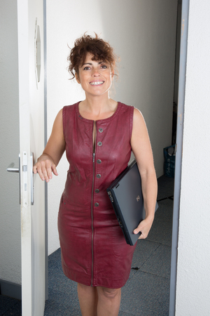 bienes raices: Business Woman opening a door and looking to the camera