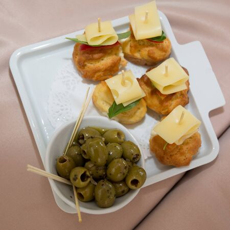 cheese bread: Green olives, slices of bread and cheese are on a white plate