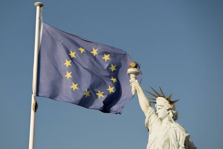 alliance: European Union flags  and Statue of Liberty, under blue sky background. Alliance. Blue sky background.