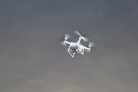 flying float: White drone hovering in a bright grey sky Stock Photo