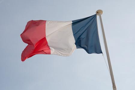 bandera francia: La bandera francesa contra el cielo nublado azul.