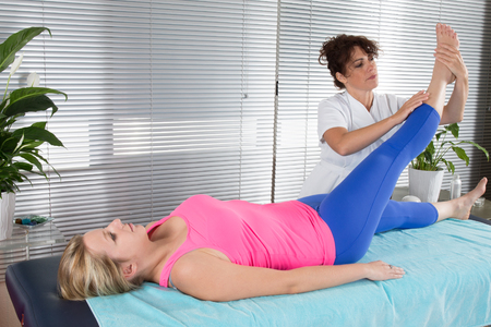 chiropractor: physiotherapy doing physical exercises with her therapist Stock Photo