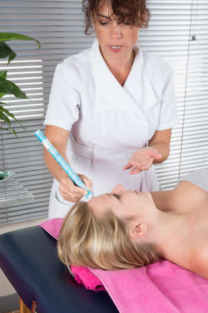 moxibustion: Detail of an acupuncture therapist using moxibustion on the back of a patient