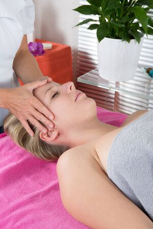 reiki: Peaceful brunette getting reiki therapy in the health spa