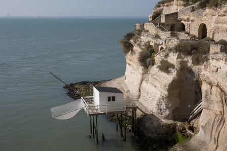 fishing cabin: View from the Gironde estuary with the limestone cliff of the village of Meschers sur Gironde and its troglodytic houses and traditionnal typical wooden fisherman cabins