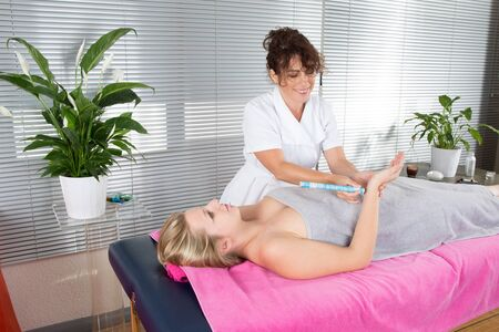 nephropathy: Physiotherapist female Massaging Palm Of A woman with moxa Stock Photo