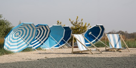 lounge chairs: Beach scene. Colorful umbrellas lounge chairs Stock Photo